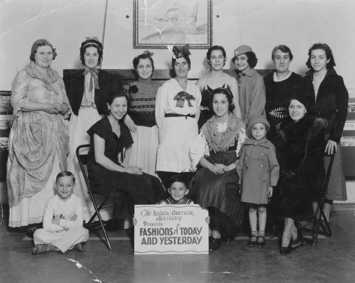 """Italian-American Auxiliary Presents Fashions of Today and Yesterday."" Grandma Mary Amelang (nee Stabile) is seated center-right, in peasant dress and shawl."